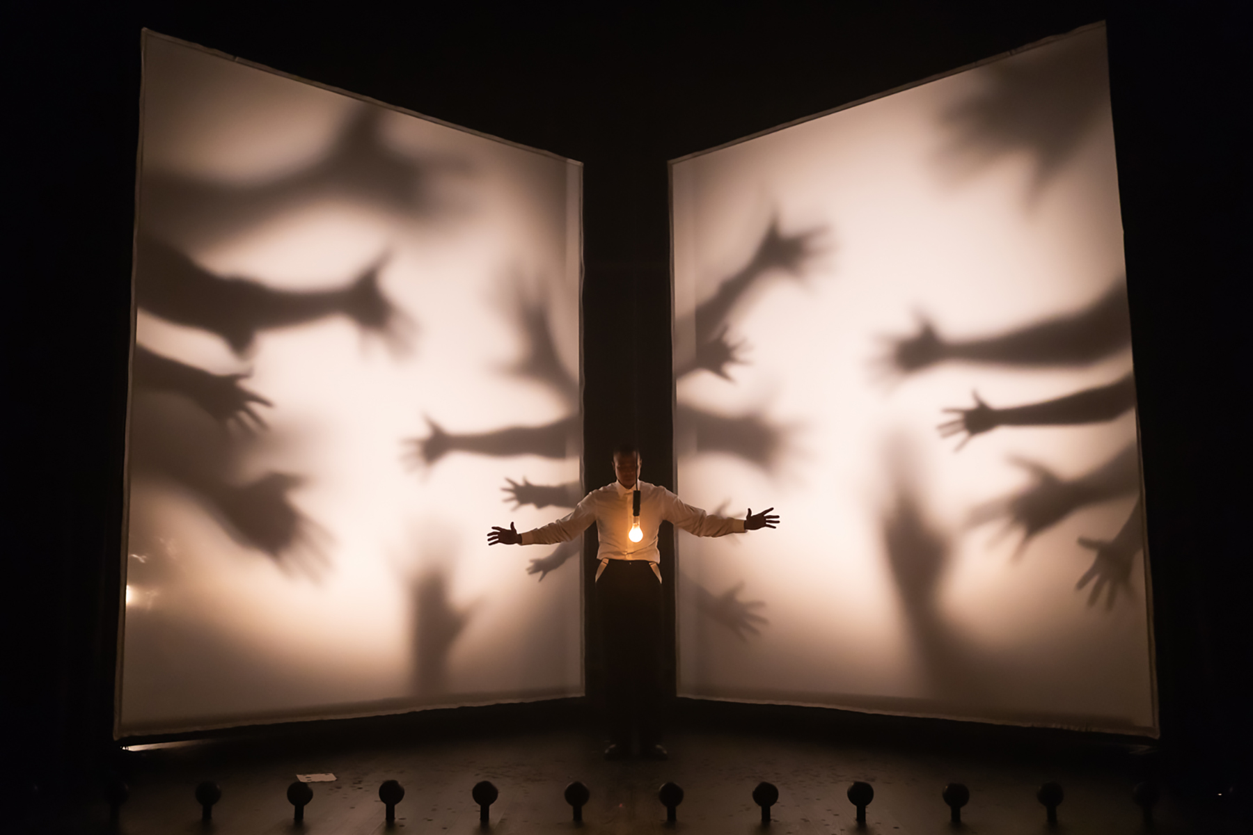 An artistic stage photo with shadows and hands from The Black Clown