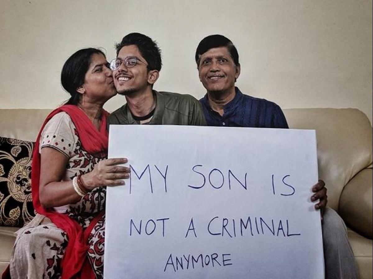 "The Mantle Image Arnab Nandy and his parents holding a sign saying ""my son is not a criminal anymore"""